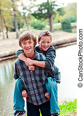 Two young boys piggy back - Portrait of Two cute young...