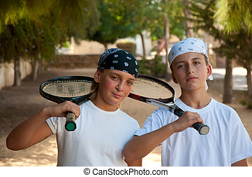 Two young boys with tennis racket .