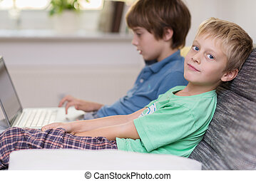 Two young brothers playing on a laptop computer