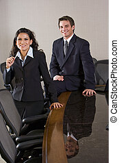 Two young business executives sitting in boardroom