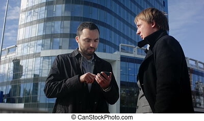 Two young business man looking offer at their smartphone