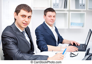 Two young business men working together at office