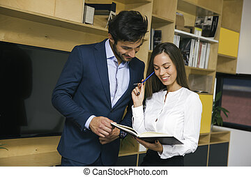 Two young business people analyzing business plan