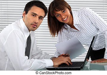 Two young business people working all hours to finish project
