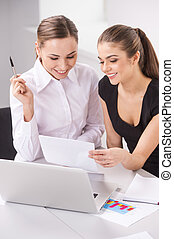 two young business woman or office workers discussing paperwork. picture of two smiling businesswomen working in office