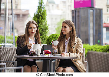 Two young business women having lunch break together