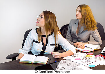 Two young business women working together