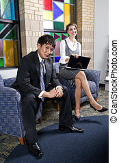 Two young business workers in office waiting room