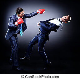 Two young businessman boxing against dark background