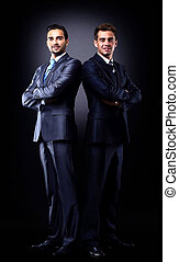 Two young businessmen full body, isolated on black