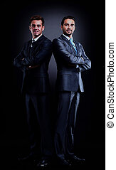 Two young businessmen full body, isolated on black.