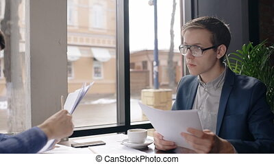 Two young businessmen is working on blueprint, sitting at table in cafe, partner passes documents to man, business people work with project during coffee break in fashionable place.