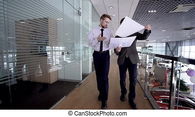 Two young businessmen looking to the reports while walking...