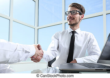 Two young businessmen shaking hands