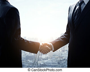 businessmen shaking hands - two young businessmen shaking...