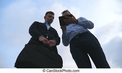 Two young businessmen talking and using tablet pc outdoor....