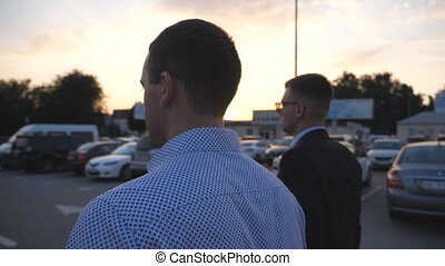 Two young businessmen walking in auto parking at sunset...