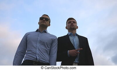 Two young businessmen walking in city with blue sky at background. Business men commuting to work together. Confident guys being on his way to office. Colleagues going outdoor. Slow motion Close up