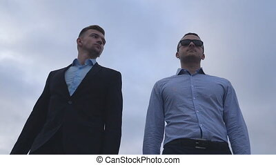 Two young businessmen walking in the city with blue sky at background. Handsome coworkers commuting to work together. Male colleagues going outdoor. Low angle view Slow motion Close up
