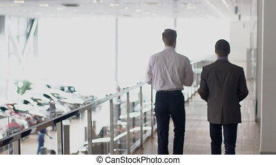 Two young businessmen walking through the gallery in...