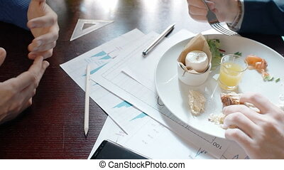 Two young businesspeople have business lunch, discussing new project, eating food, sitting at table in cafe, partners talking about work, enjoying delicious dish on desk with blueprint and phone.