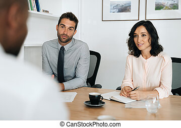 Two young businesspeople talking with a colleague in an office