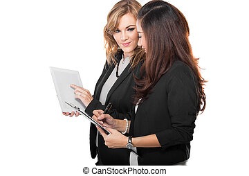 Two young businesswoman discuss with a clipboard, isolated