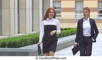 Two young businesswoman walking on the street near office building, slow motion