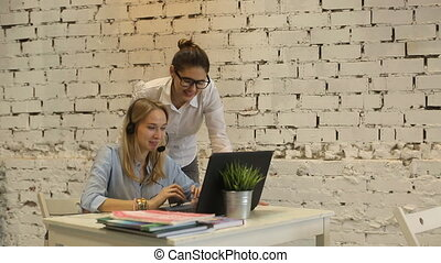 Two young businesswomen having a meeting in the office sitting