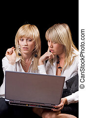 Two young businesswomen sitting with laptop. Isolated