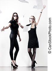 Two young businesswomen throwing out paper