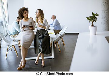 Two young businesswomen with a tablet in the office