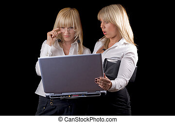 Two young businesswomen with laptop. Isolated on black