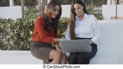 Two young businesswomen working outdoors