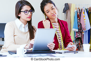 Two young businesswomen working with digital tablet in her office.