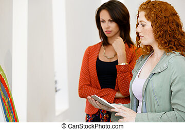 Two young caucasian women standing in art gallery front of paintings