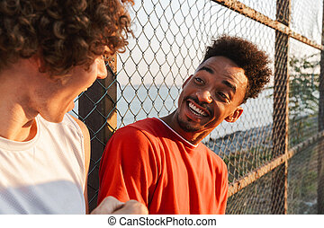 Two young cheerful multiethnic men basketball players ...