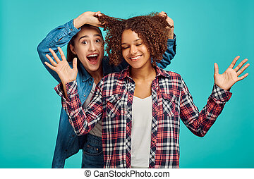Two young cheerful women, blue background, positive emotion. Face expression, female person looking on camera in studio, emotional concept, feelings