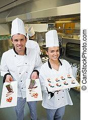 Two young chefs presenting dessert plates