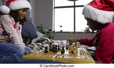 Two young chess players in santa hats indoors - Smart small...