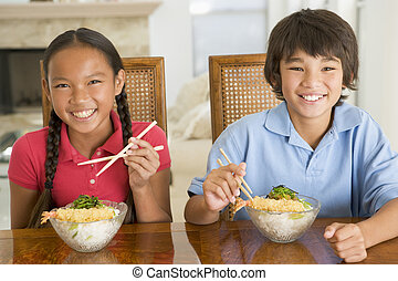 Two young children eating Chinese food in dining room...