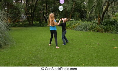 Two young children having fun hitting balloons in the air at...