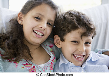 Two young children in living room smiling (high key)