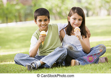 Two young children outdoors in park with ice cream smiling (selective focus)