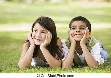 Two young children outdoors lying in park smiling (selective focus)