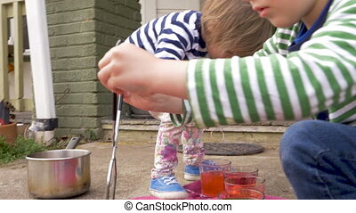 Two young children painting and dyeing easter eggs together outside