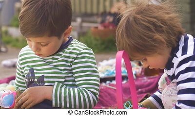 Two young children playing with toys in a basket outside...