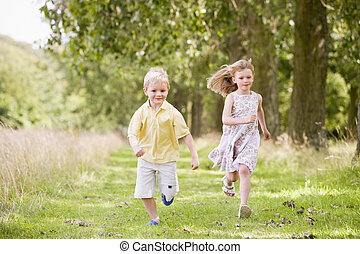 Two young children running on path smiling