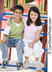 Two young children sitting on playground structure smiling (selective focus)
