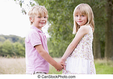 Two young children standing outdoors holding hands smiling